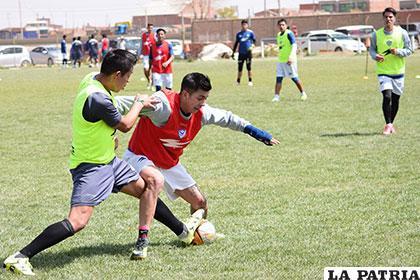 Miguel Suárez, protege el balón ante la marca de Alex Gutiérrez