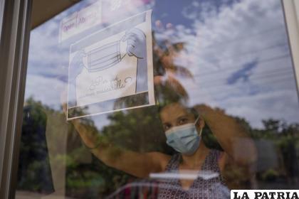 Una empleada posa cerca de un letrero que alienta el uso de mascarilla durante la pandemia de COVID-19 en la entrada de una tienda de ropa en Managua /AP Foto /Miguel Andres