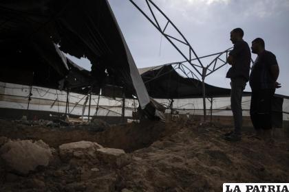 Palestinos observan los daños causados a una granja avícola tras los ataques aéreos israelíes /AP Foto /Khalil Hamra