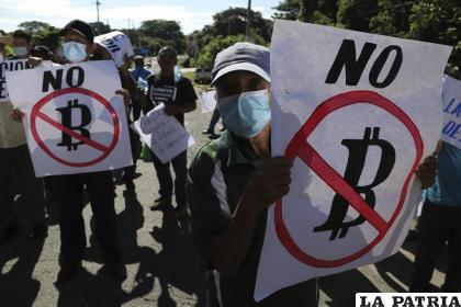 Agricultores sostienen carteles con mensajes contra la adopción del bitcoin como moneda de curso legal /AP Foto /Salvador Meléndez