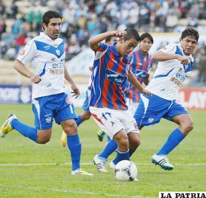 Bustillos domina la pelota ante la mirada de García y Palacios
