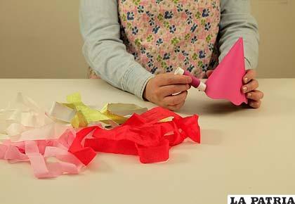 PASO 3 Comienza a poner pegamento desde la base de tu gorro de cartón, una franja a la vez