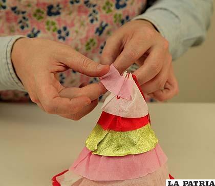 PASO 8 Tapa el hilo sobrante del pompón con más papel crepé para que tenga una bonita terminación