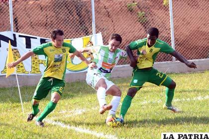 Mojica intenta eludir la marca de dos defensores
