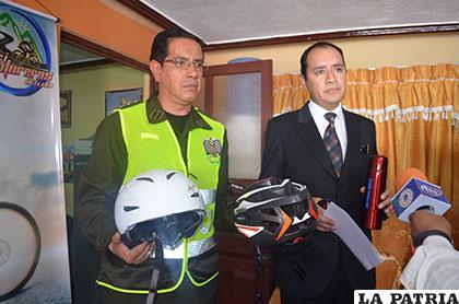 Los organizadores muestran los cascos que los ciclistas deben portar siempre que salen a manejar
