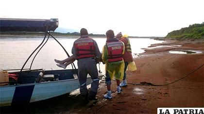 Voluntarios con el cuerpo de una de las víctimas a orillas del río Mamoré /ERBOL