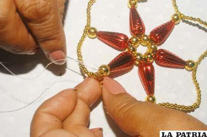 PASO 7 Ingresar por la perla de la última esquina hasta la perla del círculo, salir por un costado y enlazar la cadena de perlas por el centro de cada espacio y estirar.