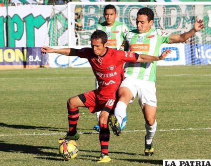 Roly Sejas y Gualberto Mojica en la acción de juego