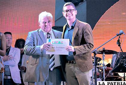 Dick entrega al gerente regional de LA PATRIA, Hasan López, el reconocimiento