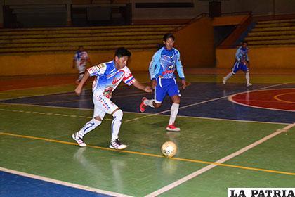 David Quisbert avanza con balón dominado ante la mirada de  Jesús López