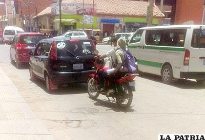 El motociclista lleva el casco de seguridad colgado en su brazo