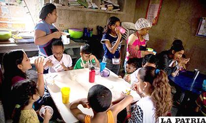 Niños comen su almuerzo en un comedor comunitario/AMAZONAWS.COM