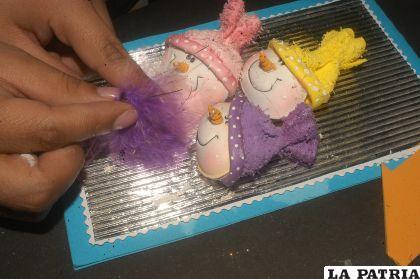 PASO 7 Pegar las cabezas en la tarjeta, como se observa en la fotografía, pegar el marabú debajo de cada muñeco, y decorar los gorritos con rosones hechos con la cinta raso del color que caracteriza a cada uno de los muñecos.