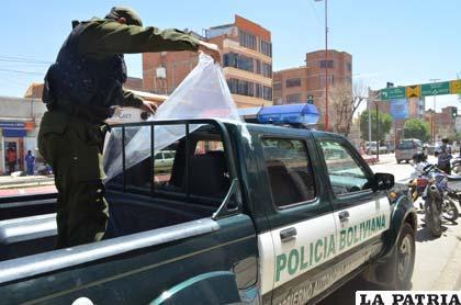 Un efectivo policial muestra el parabrisas destrozado
