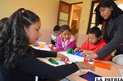 Niños aprendiendo origami en los cursos del ISBA