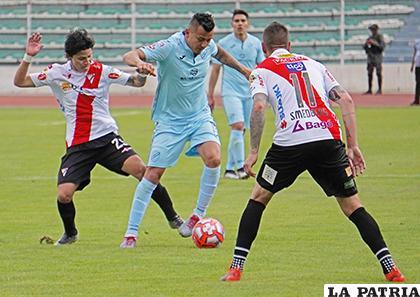 Jorge Flores, domina el balón ante la marca de sus rivales/APG